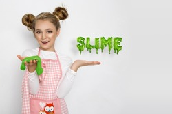 Cute funny girl with colorful slime isolated on white background. Little girl stretching pink slime to the sides. Kids hands playing slime toy. Making slime.