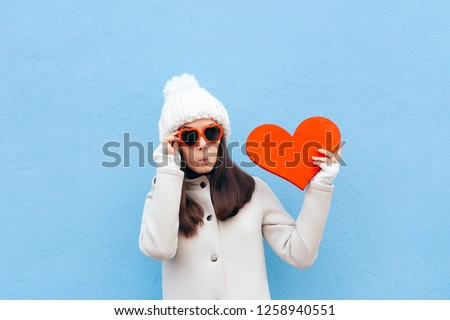 Cute Funny in Love Girl Holding Big Heart on Blue Background. Surprised romantic girl having a crush on Valentine