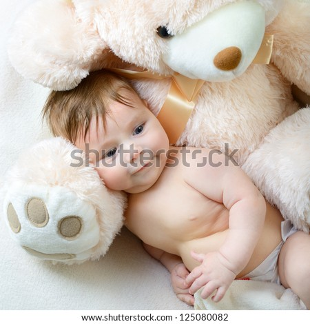 cute funny infant baby boy with big toy bear, beautiful kid's portrait closeup