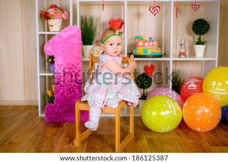 Cute funny little child in first birthday with colored balloons in the bright room