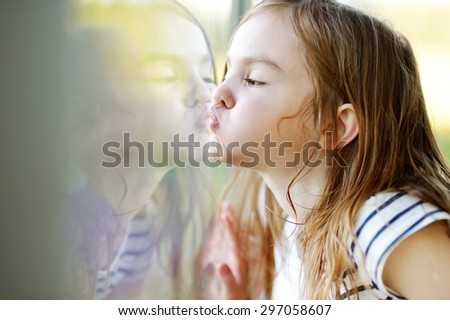 Cute funny little girl kissing her reflection on a window glass