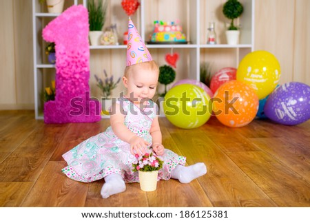 Cute funny little kid in first birthday with colored balloons - stock photo