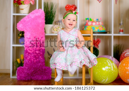 Cute funny little kid in first birthday with colored balloons in the bright room  laughing