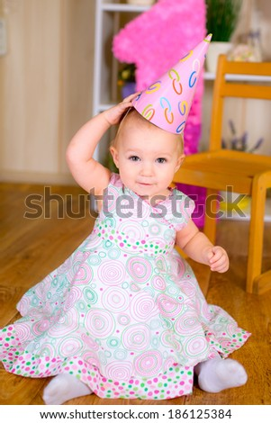 Cute funny little kid in first birthday with colored balloons in the room