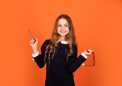 Cute genius. Girl genius brown background. Genius little child hold pen and glasses. School and education. Private teaching. Potential of mind. Creative and genius.