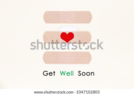 Cute get well soon card. Handmade Greeting Card Making Ideas with sticky plaster and sticker heart on yellow cream background.Top view and flat lay. #1047102805