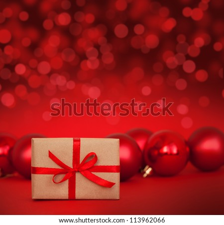 Cute gift with red christmas balls on red abstract light background