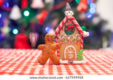 Cute gingerbread man in front of his candy ginger house background the Christmas tree lights
