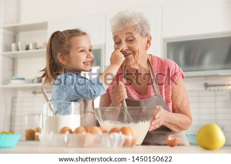 Cute girl and her grandmother cooking in kitchen Stock photo ©
