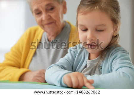 Cute girl and her grandmother reading book at home #1408269062