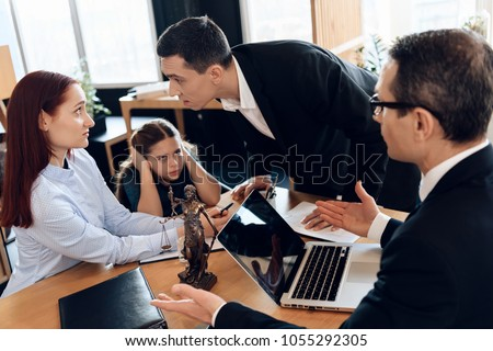 Cute girl closes ears when parents quarrel in lawyer's office. Girl's parents are getting divorced. Dissolution of marriage of two adults.