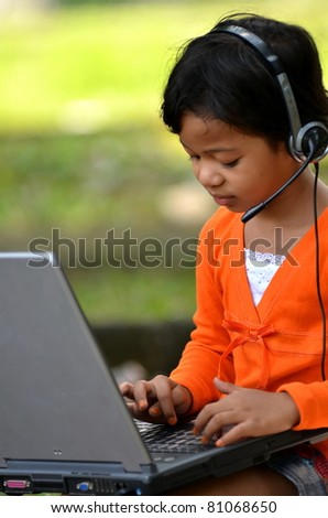 Cute girl dress in orange playing with laptop computer