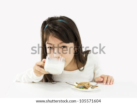 Cute girl drinking a glass of milk and eating a cake