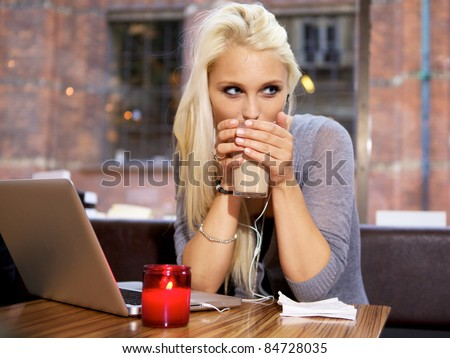 Cute girl drinking coffee on a cafe in the city.