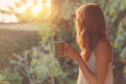 Cute girl enjoying morning coffee on the porch.