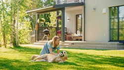 Cute Girl Has fun with Happy Golden Retriever Dog on the Backyard Lawn. She Pets, Play, Tackle it on the Ground And Scratches Back. Happy Dog Plays with Toy Ball. Idyllic Summer House.