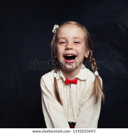 Cute girl having fun, yelling and laughing. Happy child on empty blackboard background with copy space. Back to school concept #1142033693