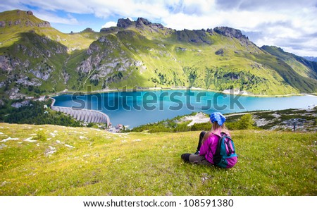 cute girl hiking in the alps pointing at a beautiful scenery