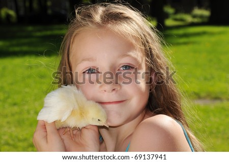 Cute girl holding little yellow chick - stock photo