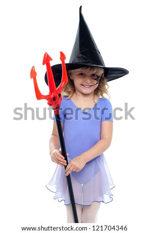 Cute girl holding pitchfork and wearing witches hat. Halloween concept