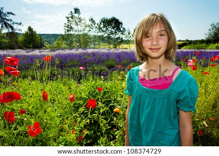 Cute girl in a field of colorful purple lavender.