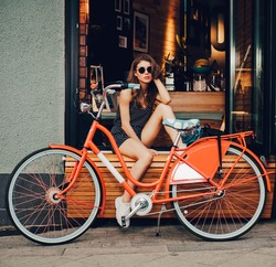 Cute girl in a summer dress is sitting with red vintage bicycle in a European city. Sunny summer. The girl in a good mood, she laughs. On background summer cafe. Outdoor. Waiting for coffee.