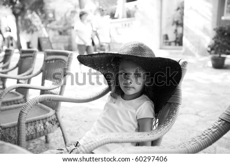 Cute girl in a wide hat in summer cafe at the street