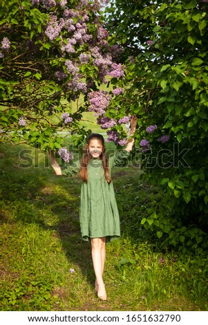 Cute girl in green linen dress has fun in the park with blooming lilacs, enjoys spring and warmth. Beautiful spring garden. Happy childhood, peace and happiness concept