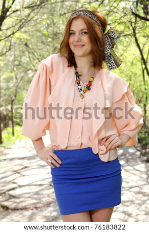 Cute girl in pink top and blue dress smiling in the park. Wears a animal print bandana.