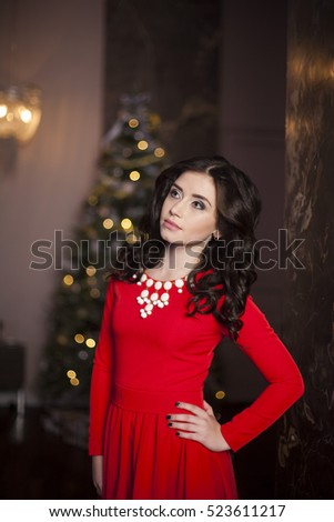 Cute girl in red dress with Christmas tree #523611217