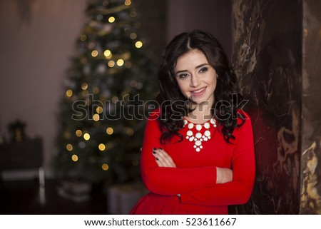 Cute girl in red dress with Christmas tree #523611667