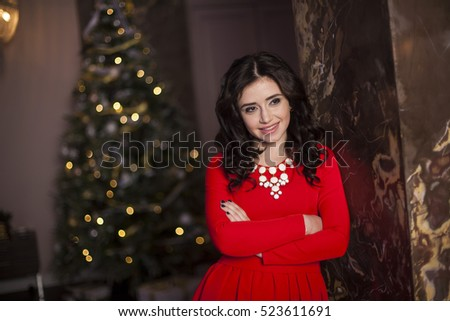 Cute girl in red dress with Christmas tree #523611691