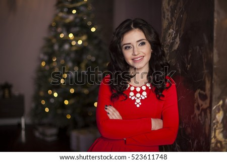 Cute girl in red dress with Christmas tree #523611748
