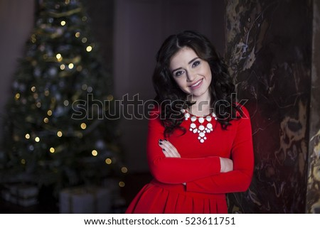 Cute girl in red dress with Christmas tree #523611751