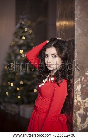 Cute girl in red dress with Christmas tree #523612480