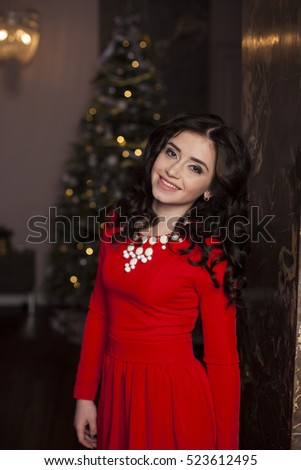 Cute girl in red dress with Christmas tree #523612495