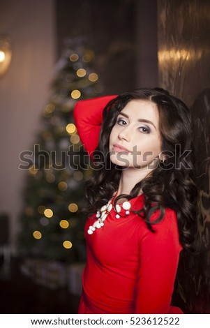 Cute girl in red dress with Christmas tree #523612522