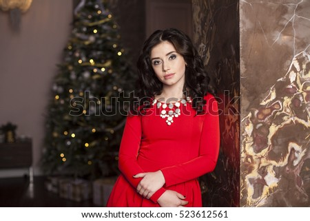 Cute girl in red dress with Christmas tree #523612561
