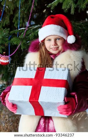 Cute girl in Santa Claus cap at a winter park. Christmas.