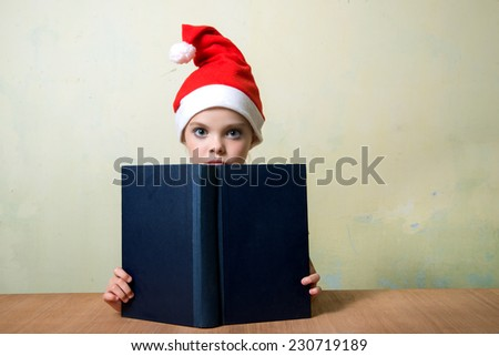 Cute girl in Santa Claus hat with big blue book.  Christmas, x-mas, New Year, Winter, people, advertisement, sale concept. Education concept.