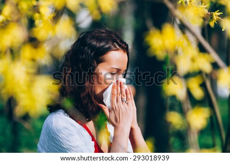 Cute girl in the park, sneezing, having spring allergies