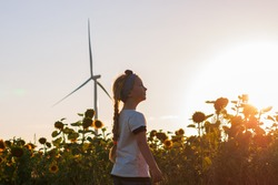 Cute girl in white t-shirt smelling sunflower in sunset field with wind turbines farm on background. Child with long braid hair on countryside landscape with yellow flowers. Farming concept wallpaper.