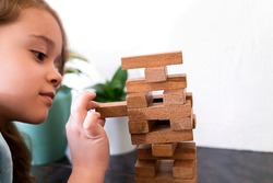 Cute girl is building a tower out of wooden blocks. Development fine motor skills in children. Child knows how to think and reason logically. Closeup of player kid.