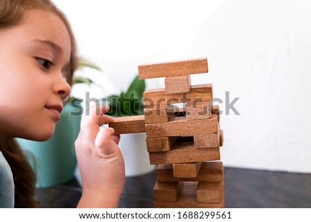 Cute girl is building a tower out of wooden blocks. Development fine motor skills in children. Child knows how to think and reason logically. Closeup of player kid. Foto stock ©