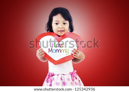 Cute girl is holding a valentine card with the word I