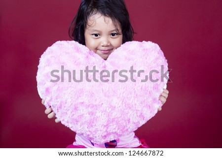 Cute girl is holding heart pillow on pink background - stock photo