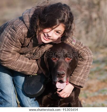 cute girl is hugging her dog