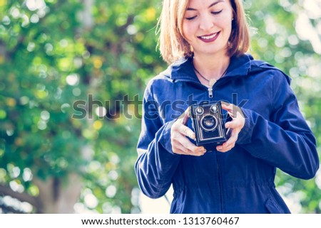 Cute girl is making pictures with a vintage camera, outside