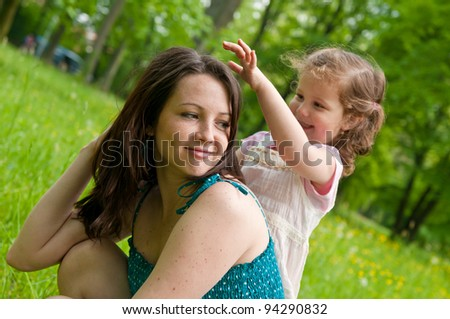 Cute girl is playing with mother's hair - outdoors scene