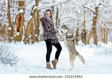 Cute girl keeps his paws dog husky on the background of the forest in winter